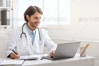 Young doctor conversating with colleagues via laptop online