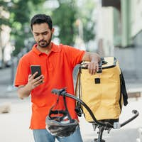 Guy courier in uniform, with beard, backpack looks at smartphone, holds bicycle and helmet