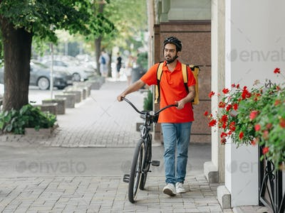 Courier with beard, helmet and yellow bag, walks with bicycle down the street