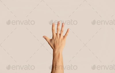 Close up of young man showing his hand, gesturing high five on light background