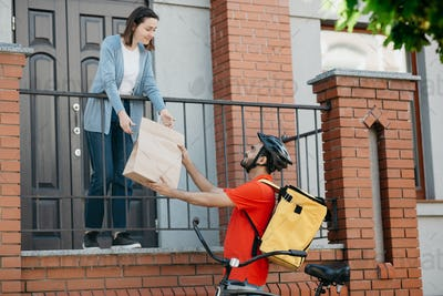 Customer, delivery and courier. Girl takes bag from man with backpack and bicycle, near front door