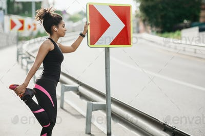 Smiling girl in sportswear and wireless headphones, leans on road sign and does exercises for leg