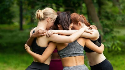 Young girls in sportswear hugging at park after morning yoga class