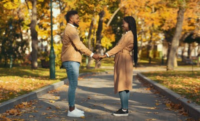 Romantic afro couple holding hands outdoors, having date in autumn park