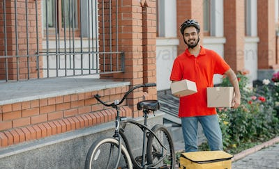 Fast delivery for many online purchases. Smiling courier with beard holds cardboard boxes