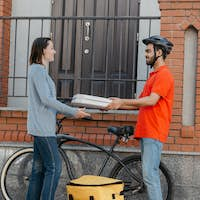 Ecological city, bike and delivering service. Smiling courier in helmet gives pizza to client, near