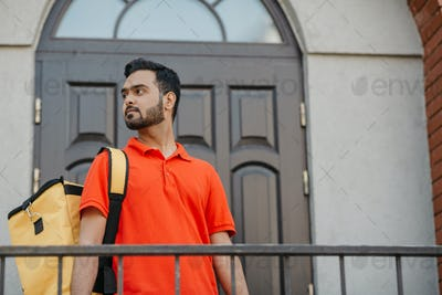 City delivery service and search customer address. Attractive man with yellow backpack, near front