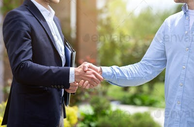 Closeup of real estate agent and his client shaking hands near new house
