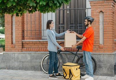 Safe delivery of purchase. Smiling courier in helmet, with big yellow backpack with bicycle, gives