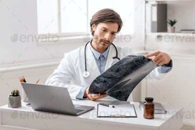 Serious medical doctor studying radiography scan at office