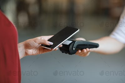 NFC Technology. Unrecognizable woman maiking contactless payment with smartphone to terminal