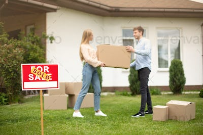 Millennial couple with carrying box in front of new home on moving day, focus on SOLD sign. Copy