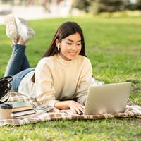 Asian woman using laptop, lying in the parkland