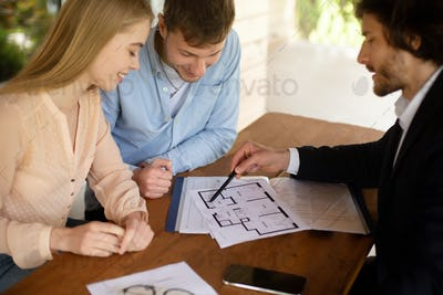 Realtor showing blueprint of new home to happy couple at table