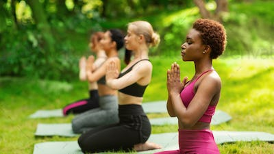 Yoga for inner peace. Group of multiracial women meditating at park in summer, blank space