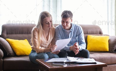 Young married couple looking through tenancy agreement in house for sale