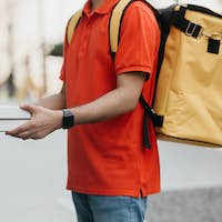 Takeaway and delivery. Delivery man with backpack, smart watches give boxes with pizza for girl in