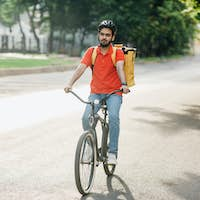Modern delivery in city. Young man in helmet with bag rides on bicycle