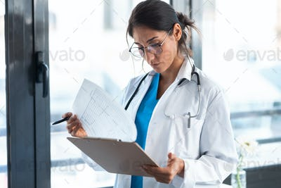 Beautiful female doctor reviewing medical documents while standing in the consultation.