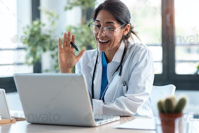 Female doctor waving and talking with colleagues through a video call with a laptop