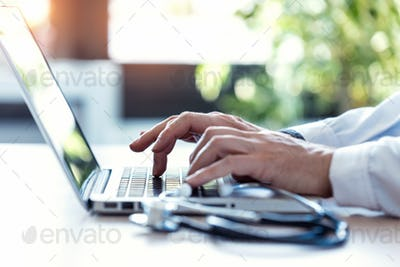 Hands of unrecognizable doctor writing on a computer.
