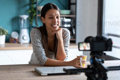 Smiling young woman doing a video blog with the camera in the kitchen.