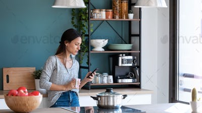 Concentrated young woman using her mobile phone in the kitchen.