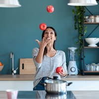 Funny young woman juggling with three red apples in the kitchen at home.