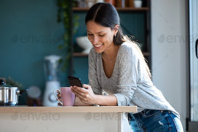 Smiling young woman using her mobile phone while drinking a cup of coffee in the kitchen at home.