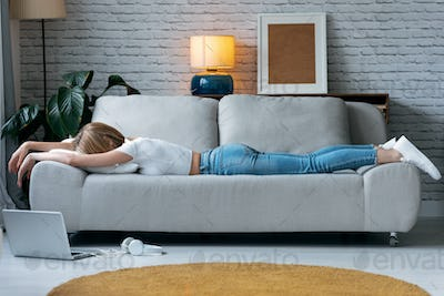 Exhausted young woman lying down on sofa at home.