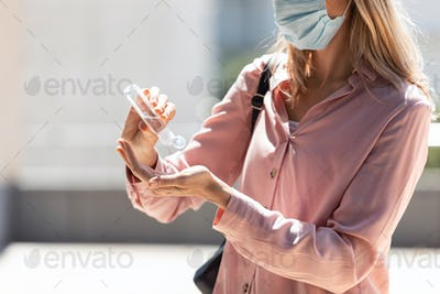 Woman cleaning her hands with sanitizer in the street.