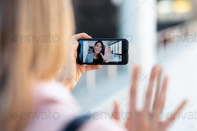 back view of woman having video conversation with pretty young business woman