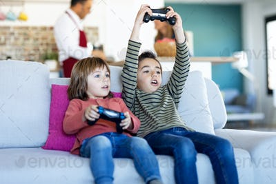 Two nice brothers playing video games while sitting on the sofa at home.