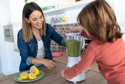 Boy helping his mother to prepare a detox juice with blender in the kitchen at home.