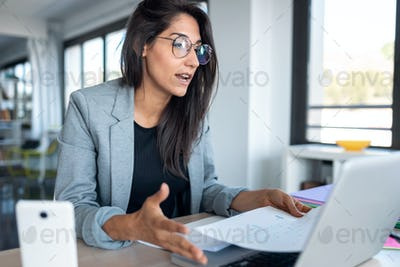 confident business woman looking and speaking through the webcam while making a video conference