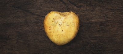 Heart shaped potatoes ion wooden background, top view
