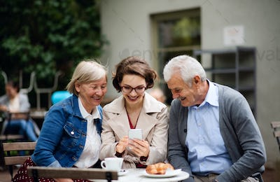 Woman with senior parents sitting outdoors in cafe, using smartphone