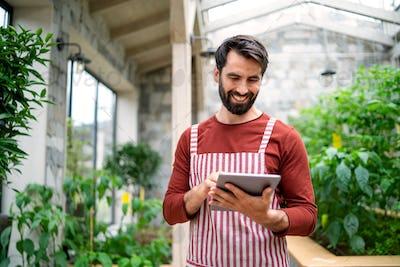 Man gardener with tablet standing in greenhouse, working