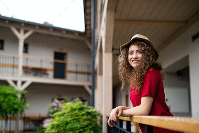 Young woman standing outdoors on hotel balcony on holiday, relaxing