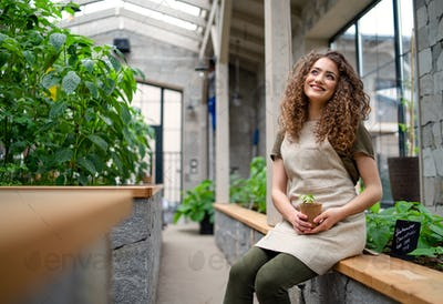 Woman gardener sitting in greenhouse, holding small plant