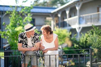 Senior couple holding wine outdoors on holiday, talking