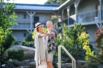 Senior couple dancing outdoors on holiday, having fun