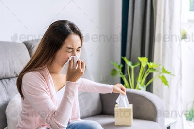 Young asian women with allergies feeling unwell using tissues and sneezing at home