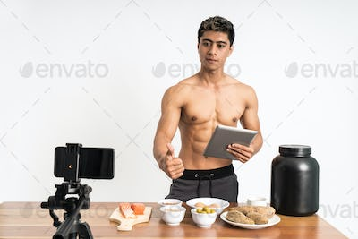 muscular man health and sports blogger with thumbs up showing healthy food menu while holding a pad