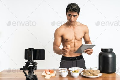 man health and sports blogger showing healthy food menu while holding egg and tablet
