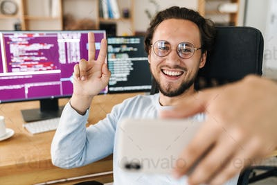 Image of programmer man gesturing peace sign while taking selfie photo