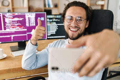 Image of programmer man showing thumb up while taking selfie on cellphone