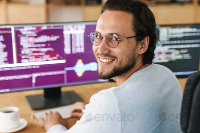 Image of smiling unshaven programmer man working with computers