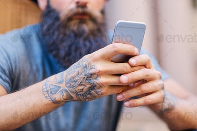 Bearded male in a hat holds a smartphone.