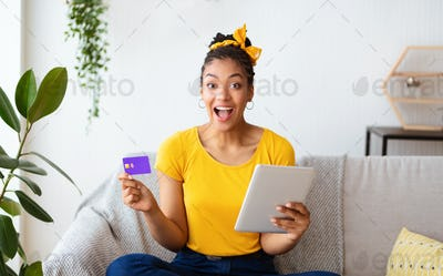 Black lady using tablet and credit card at home